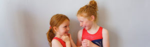 Two children sharing a giggle at summer theatre school