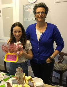 Child and parent with cakes for Macmillan Cancer Support
